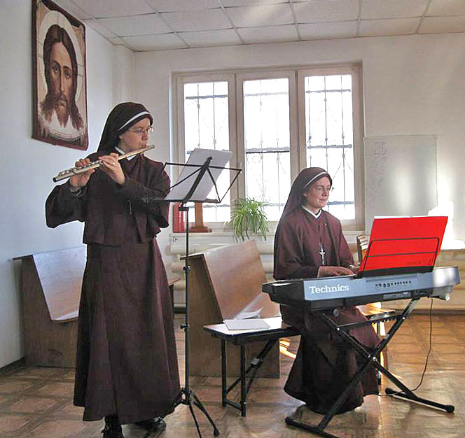 Sisters practicing music on flute and keyboard.
