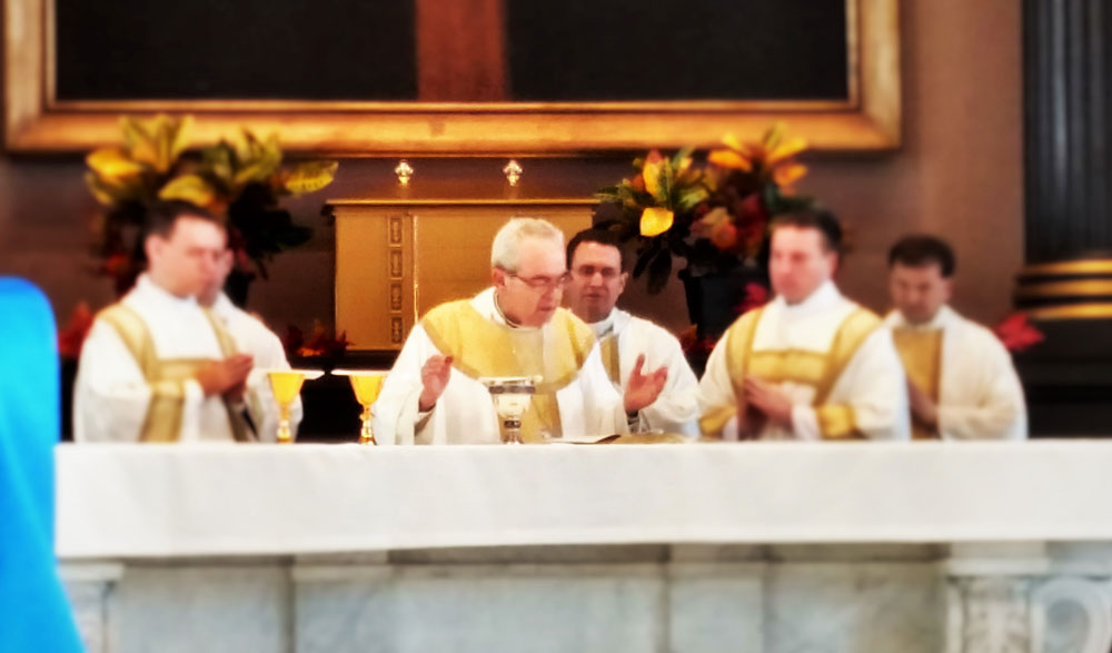 Cardinal Rigali and priests at altar